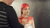Makeup artist covering girls body with red paint