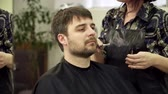 Hairdreser is trimming mans beard in salon