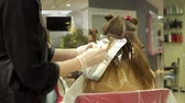 Young woman is having her hair colored in salon Stock Footage
