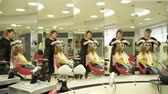 Hair stylist is dyeing girls hair in front of the mirror