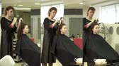 Hairdresser is combing young womans hair Stock Footage