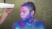 perfection : Makeup artist is covering mans hair with pink powder