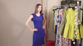 ponderar : Charming model under the camera flashes presenting blue dress in the studio slow motion