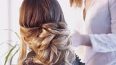 slomo : Hairdresser creating a hairstyle for a beautiful woman in hair salon