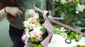 decorador : Florist wrapping a bouquet with paper for decoration in flower shop