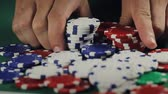 gamble : Poker All In Chips. 2 clips.  first clip is a dolly shot from left to right of a poker table with chips falling into center pot.  second clip is an overhead dolly in shot of hands placing all poker chips into center pot.  slow motion. shallow depth of fie Stock Footage