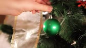 неузнаваемый : Green Ornament Place Dolly. camera dollies left as a person places a green ornament on a Christmas tree. Camera stays on Ornament. slow motion