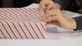 неузнаваемый : Dolly Fold Wrapping Paper. camera dollies to the left as someone folds ends of wrapping paper over a present corner Стоковые видеозаписи