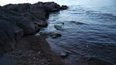 причал : Waters Edge. selective focus on rocks in the water. waves roll up on a jetty on a lake.