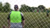 неузнаваемый : Net and Goalie from Behind. shot from behind a net with a goalie ready for action. focus is on net.