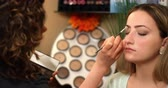 make up applying : Make-up Artist Darkens Eyebrows Dolly Left. camera moves left and racks focus from flowers in the foreground to client receiving make-up in salon. Stock Footage