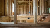 Second Floor Residential New Home Construction. camera moves right on a new under construction home. shot from upstairs room. shows framing and bare beams for roof. architecture and construction Stock mozgókép