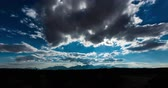 típico : Sun Behind the Clouds Time Lapse. a time lapse of a mountain range in New Mexico with clouds forming and covering the sun