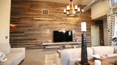 mesa de madeira : Rising Shot of Modern Living Room Door Close. camera moves from a floor angle to reveal a modern living room and outside garage style door closes. Large reclaimed wood wall Vídeos