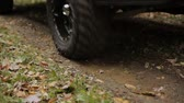 Closeup of Truck Driving Through a Mud Puddle. an angled shot of truck tires driving through a mud puddle in the rain