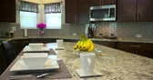 steel : Kitchen Island Move Left Medium Shot. camera moves left on the granite kitchen island set up for a meal Stock Footage