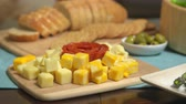 queijo cheddar : Cubed Cheese Rack Focus Crackers. camera racks focus from sliced bread and cracker spread to cubed cheese variety and pepperoni, then back again. Olives in scene too Vídeos