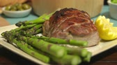 pork meat : Pork Roast Close Up Rack Focus. camera racks focus from the front to back of a pork roast with asparagus on a plate with lemon