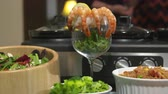 rice dishes : Shrimp Cocktail Move Left. camera moves left and spins keeping focus on shrimp cocktail display on a table surrounded by a variety of food dishes