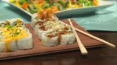 asya mutfağı : Sushi Close Up Move Right  and Left on a Table Spread. camera moves right and left over a variety of sushi with chop sticks, surrounded by a variety of other foods for a party Stok Video