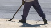 flatten : Asphalt Worker Scraping Ground with Shovel. A slow motion shot of Pavement Construction workers cleaning an asphalt area before paving