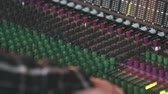 állítsa : Follow Hands on Audio Board Hand Held. a hand is adjusting knobs on a recording audio board and follows hand down Stock mozgókép
