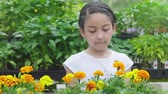 Young Girl Walks in and Smells Flowers and Smiles. a slow motion shot of a girl in a flower shop smelling flowers and smiling at camera