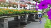duas pessoas : Girls Skipping in Flower Nursery Shop. a slow motion view revealing two girls skipping down the aisle of a flower shop smiling Stock Footage