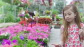 Young Girl Chooses Flower and Smells. a slow motion view of a girl walking down a line of flowers choosing some to smell and smile at camera