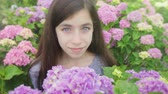 Girl Smells Flower and Looks Up and Smiles. a close up view of a girl in a group of flowers and smells one and looks up at camera and smiles