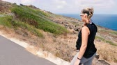 Girl Walking Along Ocean Trail Looking Out. a rising shot of a woman walking on the makapuu trail in Hawaii looking out Stock mozgókép