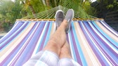 Hammock Swing Point of View Tlit Down. a slow motion personal point of view of a male swinging on a hammock, tilt down from palm trees to legs on hammock Stock mozgókép