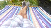 Hammock Swing Point of View Tlit Up. a slow motion personal point of view of a male swinging on a hammock, tilt up from legs on hammock to palm trees Stock mozgókép