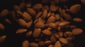 elszórt : Almond Nuts Flying in the Air in a Free Fall in Slow Motion on Black Background at 1500 fps Stock mozgókép