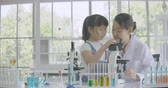 Asian female scientist teaching little girl scientific experiment using microscope in classroom laboratory.