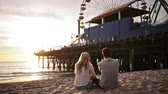 doca : romantic couple watching sunset at santa monica
