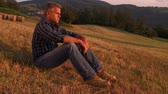 pasture : Mature man taking a break and relax in a meadow in the wonderful warm light of the sunset. Man lying in a field.