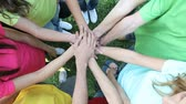 forming : Happy joyful friends forming a circle with their hands in center on grass. Closeup of stack of hands. Teenagers putting their hands on top of each other symbolizing unity and teamwork. Happy Teenage Group with Hands on Stack outdoor. Stock Footage