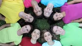 unidade : Happy joyful group of frined staying together outdoor. Smiling teenagers forming a circle of head lying on back. Portrait of group of people exults lying on grass at park and looking at camera.