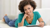 tabuleta digital : Portrait of young happy african woman looking at digital tablet. Girl lying on front on couch using a digital tablet and looking at camera. Smiling african teenager relaxing on sofa at home with digital tablet.