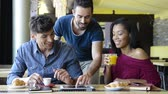 showing : Closeup shot of happy young friends using digitaltablet during breakfast. Smiling men and woman doing breakfast at coffee bar. Happy young friends looking at palmtop and having a joyful breakfast.