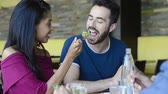 выстрел : Closeup shot of young woman feeds salad to her boyfriend. Friends having meal together. Happy young friends eating salad at restaurant. Стоковые видеозаписи