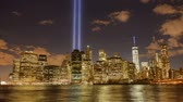 illuminated : Time lapse 4K video of the Tribute in Light to commemorate the September 11, view  of the Financial District, Manhattan, New York City. Timelapse video of Lower Manhattans skyline from DUMBO in Brooklyn during 911, zoom in. Two beams of light over NYC.
