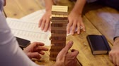 ajuda : Close up of hands helping build a building of wooden pieces. Businesspeople planning a new business strategy. Business team trying to generate new ideas with the help of playing with wooden bricks. Business risk concept.