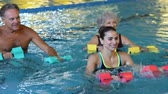 piscina : Happy active fitness mature man and senior woman doing exercise with aqua dumbbell in a swimming pool with instructor. Retired people doing aqua gym exercise with water dumbbell in swimming pool and looking at camera.
