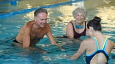 gym : Happy smiling mature man and old woman cycling on a swimming bike in swimming pool. Happy and healthy senior people enjoying swimming with young woman. Fitness class doing aqua aerobics on exercise bikes in a swimming pool.