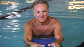 gym : Happy senior man with kickboard in a swimming pool. Old man swimming in water with the help of a kickboard. Smiling elderly man swimming with inflatable board in swimming pool looking at camera.
