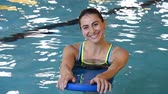 ginásio : Happy young woman with kickboard in a swimming pool. Portrait of beautiful woman swimming in water with the help of a kickboard. Smiling girl swimming with inflatable board in swimming pool and looking at camera.