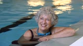 mais velho : Portrait of elderly woman against the edge of a swimming pool and looking at camera. Fit and active senior woman enjoying retirement in the swimming pool. Beautiful mature woman relaxing in the swimming pool.