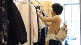 Young american woman in boutique selecting new clothes to buy. Happy smiling african girl with curly hair looking at clothes in a fashion store. African woman doing shopping in a new clothing store and checking the prices. Стоковые видеозаписи